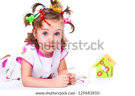 Funny preschool girl playing with bird house decoration - stock photo