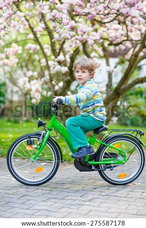 Funny preschool kid boy having fun his first bike in park or garden on warm spring day. Happy child in colorful clothes. Active leisure for kids outdoors. - stock photo