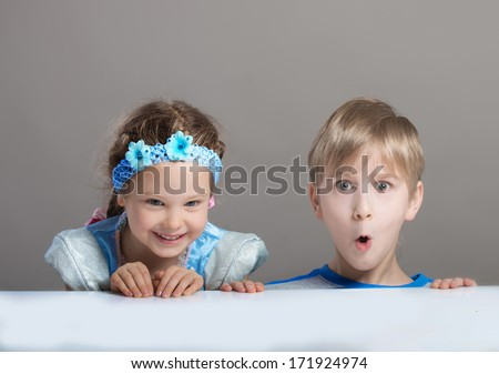 Funny preteen boy and smiling 4-year-old girl looking at camera from behind the table - stock photo