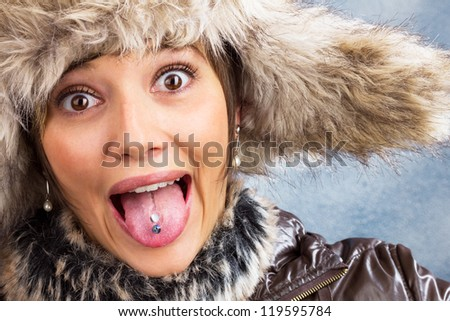 Funny pretty woman with tongue piercing in winter clothes making grimaces. Studio shot against a light blue background