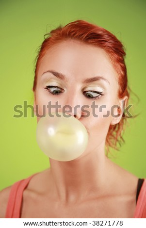 funny redhead girl with bubble gum on green background