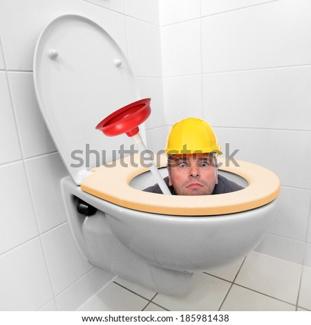 Funny repairman looking from the toilet bowl. - stock photo