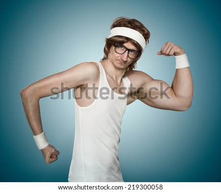 Funny retro nerd with one huge arm flexing his muscle over blue background - stock photo