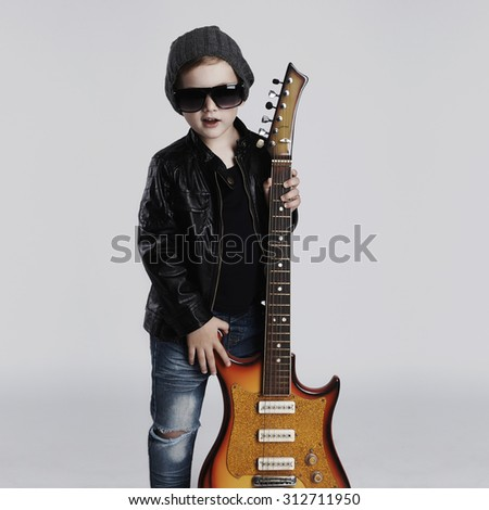 Funny rock child with guitar.fashionable little boy in sunglasses.stylish kid in leather coat. music concept - stock photo