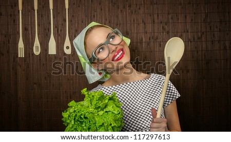 Funny rural woman cook holdin ledle and salad, close-up