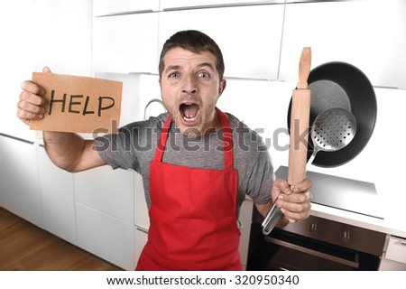 funny 30s Caucasian man holding pan and rolling pin wearing red apron at home kitchen asking for help unable to cook showing and screaming in cooking panic with funny face expression - stock photo