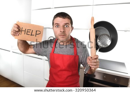 funny 30s Caucasian man holding pan and rolling pin wearing red apron at home kitchen asking for help unable to cook showing panic and stress on  cooking with funny face expression - stock photo