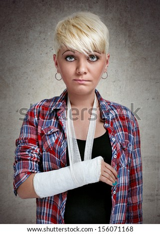 funny sad girl with holding her painful  broken arm - stock photo