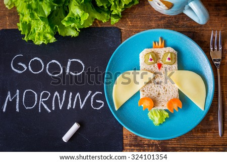 Funny sandwich owl for kids on plate, black chalkboard with Good morning greeting. healthy breakfast. Wooden table background  - stock photo