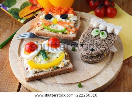 Funny sandwich with faces for kids. Colorful and healthy breakfast - stock photo
