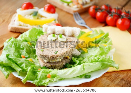 Funny sandwiches for kids. Healthy colorful breakfast, lots of vegetables, green salad and whole grain bread on wooden table - stock photo
