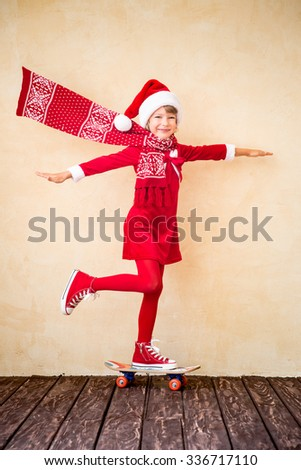 Funny Santa kid with flying scarf riding skateboard. Christmas holiday concept - stock photo