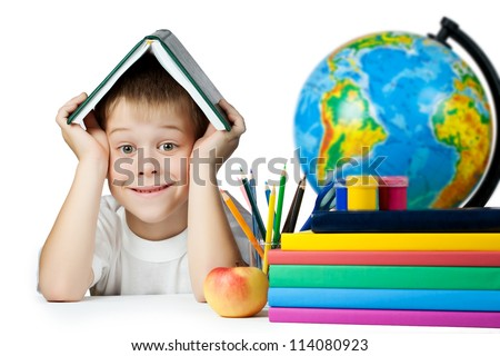 funny schoolboy with a book on her head. isolated