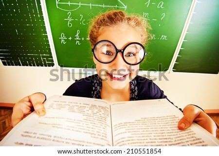 Funny schoolgirl in big round glasses opened the book and looking at the camera. Education. - stock photo