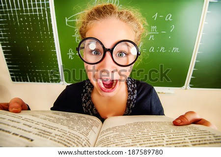 Funny schoolgirl in big round glasses opened the book and shouting at camera. Education. - stock photo