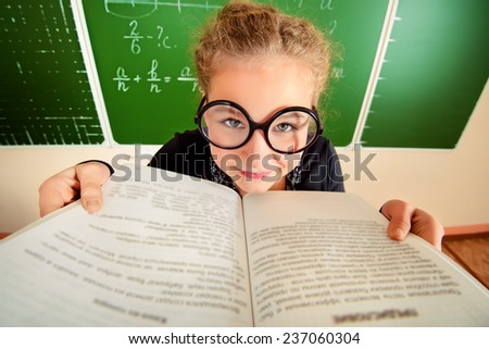 Funny schoolgirl in big round glasses opened the book and stares at the camera. Education. - stock photo