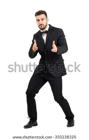 Funny secret agent shooting at camera with handgun pistol finger sign. Full body length portrait isolated over white studio background. - stock photo