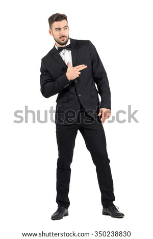 Funny secret agent with finger gun hand gesture looking away. Full body length portrait isolated over white studio background.