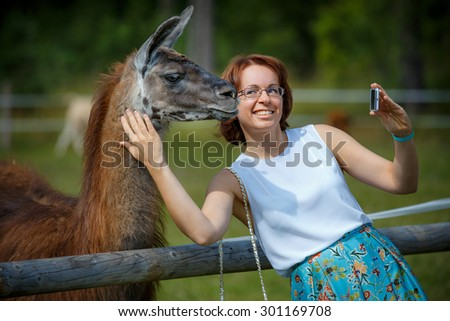 Funny selfie with my friend. Attractive smiling young woman holding smartphone and making selfie with lama outdoors - stock photo