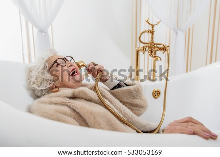 Funny Senior Lady With Fur Coat In Bathtub