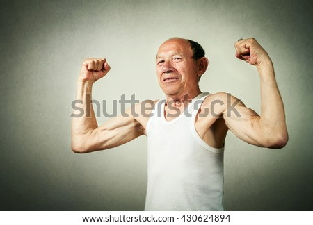 funny senior man showing the muscles - stock photo