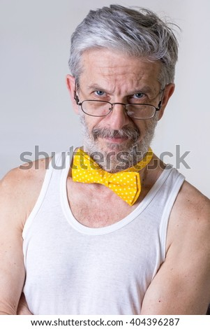 Funny senior man with a bow tie around his neck