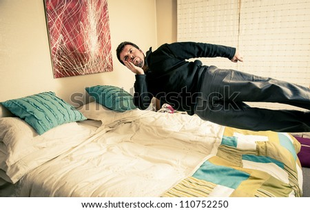 Funny shot of a man thinking but flying over his bed. - stock photo