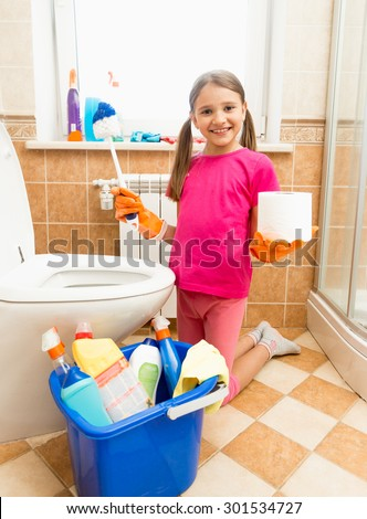Funny shot of smiling girl posing with toilet paper and brush at bathroom