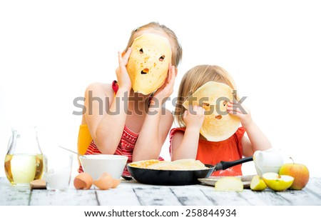 funny sisters cooking pancakes on kitchen - stock photo