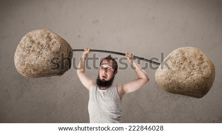 Funny skinny guy lifting large rock stone weights - stock photo
