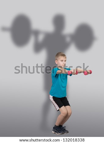 Funny slim boy doing squat exercises with weightlifter's silhouette behind him - stock photo