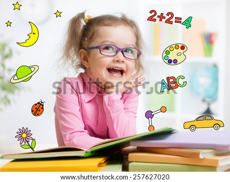 Funny smart kid in eyeglasses reading book in kindergarten - stock photo