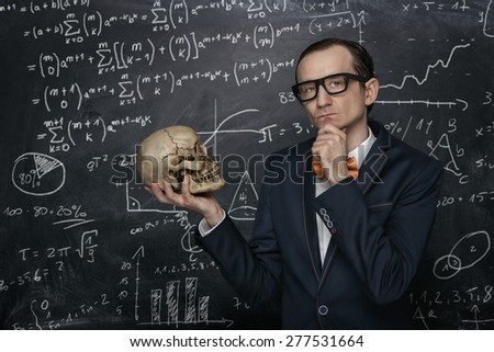 Funny smart nerd against chalkboard background with many math formulas - stock photo