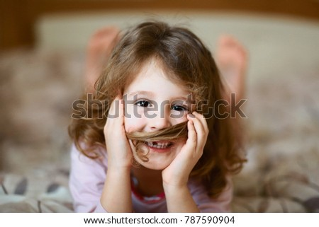 funny smile of a little curly girl without front teeth, a cheerful preschooler, a beautiful girl with milk teeth dropped out with a hair mustache