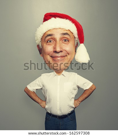 funny smiley senior man in red santa hat over grey background
