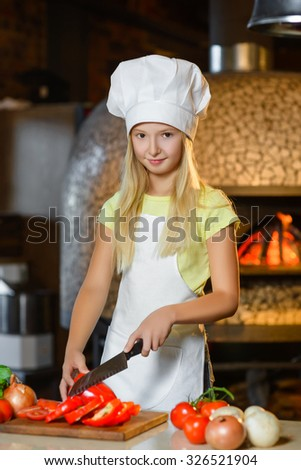 Funny smiling chef girl cuts pepper at restaurant kitchen - stock photo