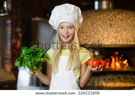 Funny smiling chef girl holding tomatoes and basil at restaurant kitchen - stock photo