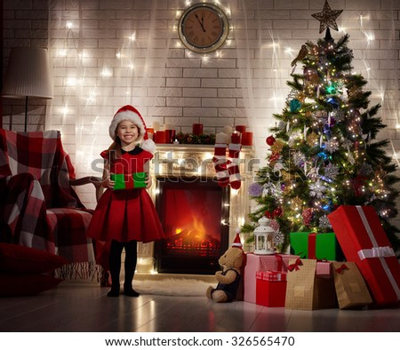 Funny smiling child holding Christmas gift in hand. - stock photo