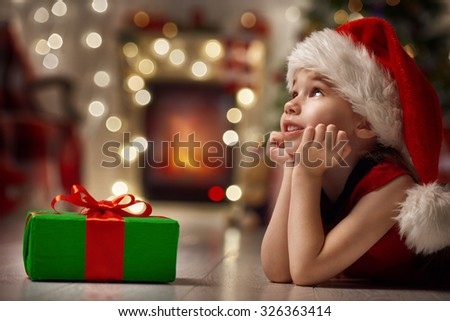 Funny smiling child in Santa red hat - stock photo
