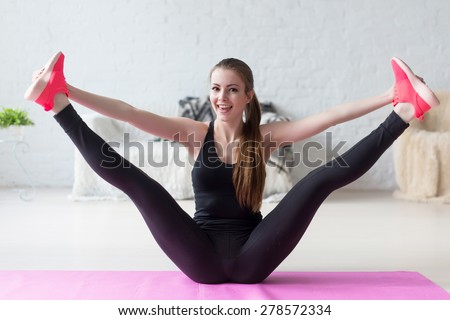 Funny smiling girl holding legs apart doing exercises aerobics warming up with gymnastics for flexibility leg stretching workout at home fitness - stock photo