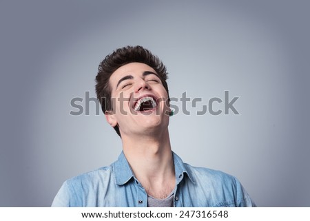 Funny smiling guy laughing out loud with closed eyes - stock photo