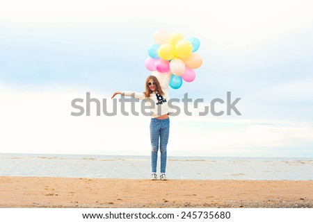 Funny smiling happy girl with many colored air balloons on the seaside. Outdoors. Filtered image. - stock photo