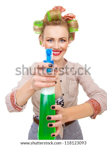 Funny smiling housewife / woman spraying the cleaner on you, isolated on white. Glass or window cleaner