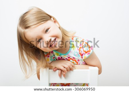 Funny smiling little girl sitting on a chair. Isolated over light gray background. - stock photo