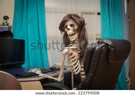 Funny smiling skeleton sitting  in room behind the desktop computer - stock photo