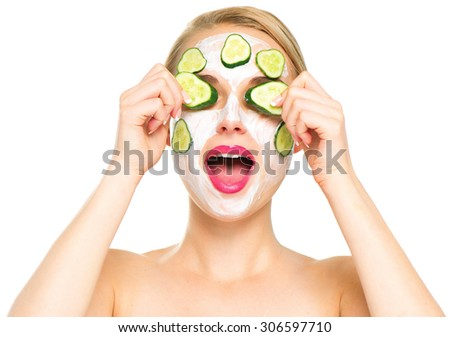 Funny smiling Spa Woman applying fresh Facial Mask with cucumbers. Beauty Treatments. Face mask, skin care concept. Beautiful Woman Applying Natural Homemade Facial Mask - stock photo