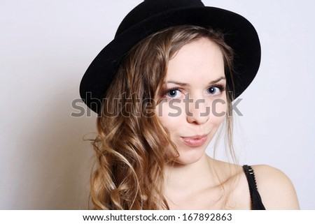 funny smiling woman with curls and blue eyes in hat. studio
