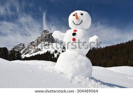 Funny snowman against Swiss Alps - stock photo