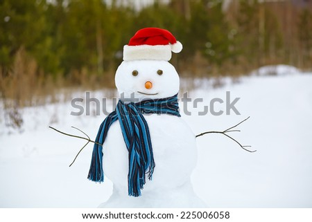funny snowman in a forest. snowman in santa hat outdoors - stock photo
