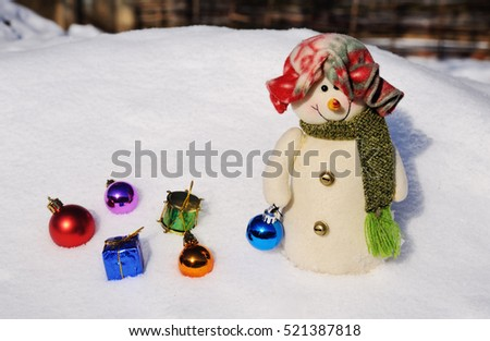 funny snowman in a hat with Christmas toys on a background of snow drifts
